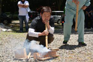 火起こしの実演② 種火に空気を送り火を起こします。