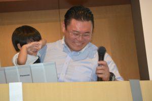 我慢できずに壇上に上がってきたお子さんを抱っこしながらの本日のまとめ(*お子さんは、中島委員長のお子さんでのありません。)