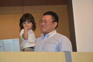 またまた壇上に上がってきたお子さんを抱きかかえながら、川北理事長の謝辞を聞く中島委員長(*このお子さんも、中島委員長のお子さんではありません。)